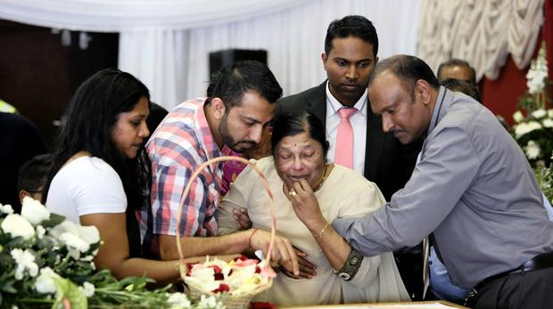 Dhasogan Pillay (back), watches as relatives mourn over the coffin of his mother, Gona.