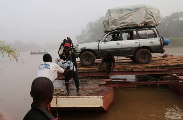 Migrants expelled from Angola cross a river on the road to DR Congo