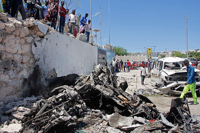 Somalis look at the wreckage after a suicide car bomb attack in the capital Mogadishu