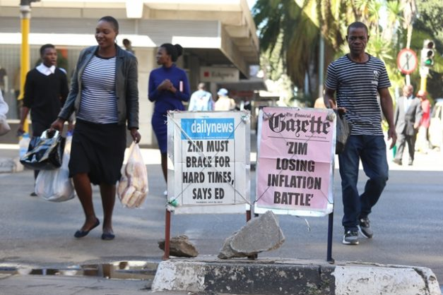 eople walk near newspaper posters on Zimbabwe's current economic situation in Harare, Zimbabwe, 25 July 2019. Picture: EPA-EFE / AARON UFUMELI